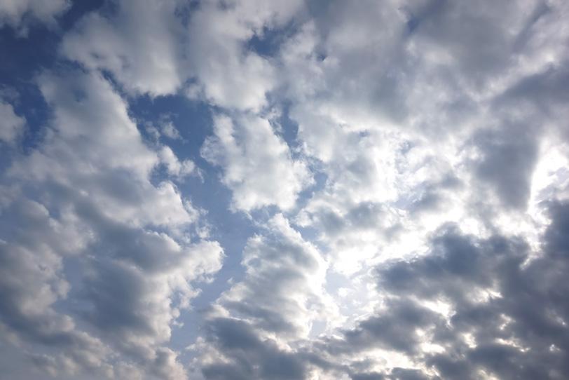 日に被さる綿雲の群れの写真画像