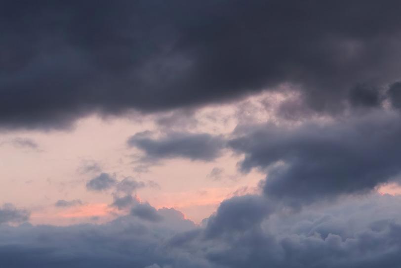 暗雲の向こうに見える薄紅色の空の写真画像