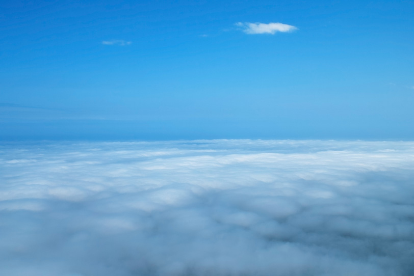 青空の下に雪原の様に広がる雲の写真画像