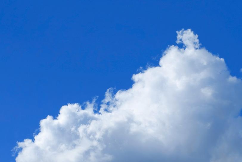 三角雲とベタ塗りの青空の写真画像