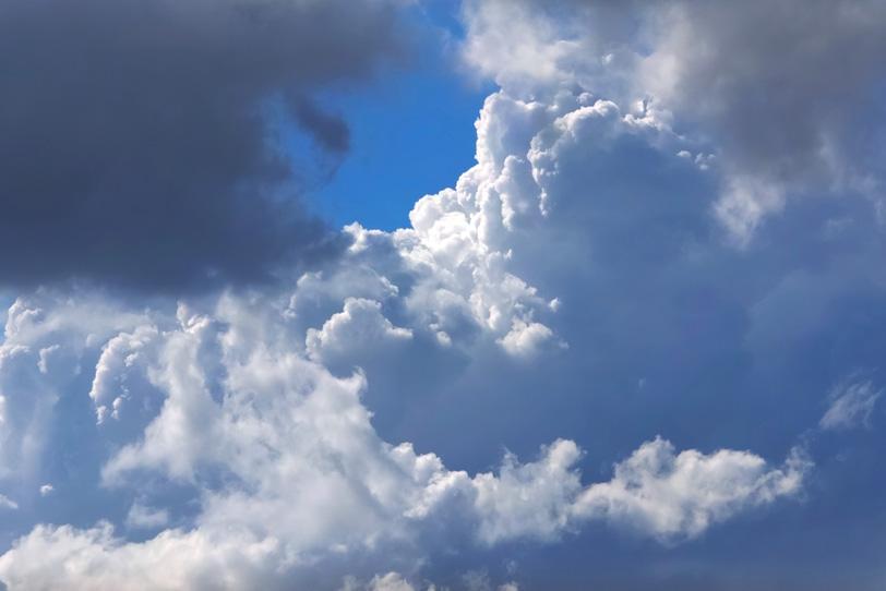 見上げる積乱雲と小さな青空の写真画像