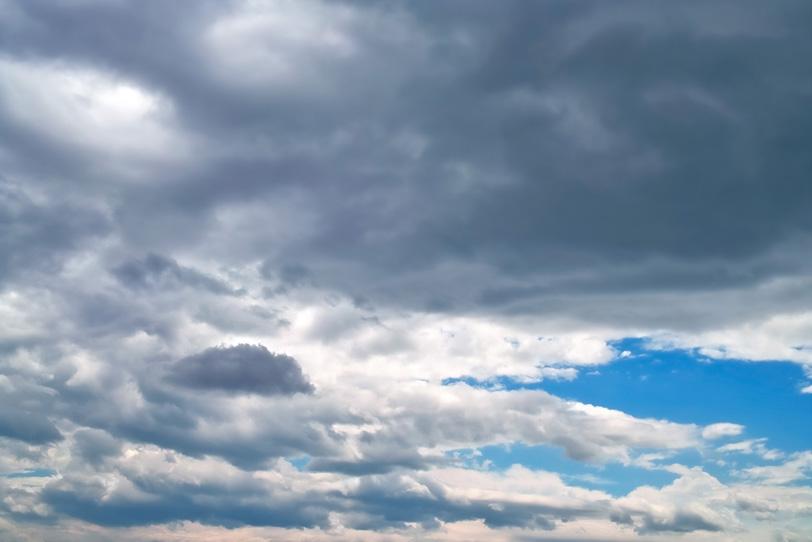 暗雲が流れ込む青空の写真画像