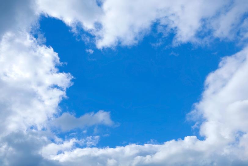 雲のフレームが飾る清澄な青空の写真画像