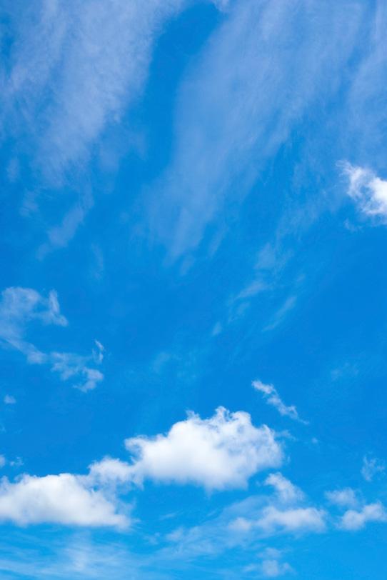 綿雲と流れ落ちる様な雲がある青空の写真画像