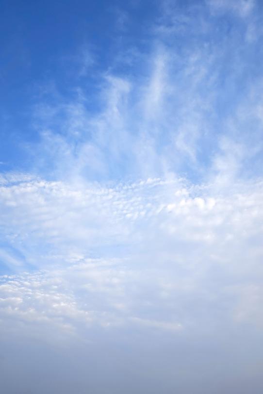 叢雲の青空に湯気のような巻雲の写真画像