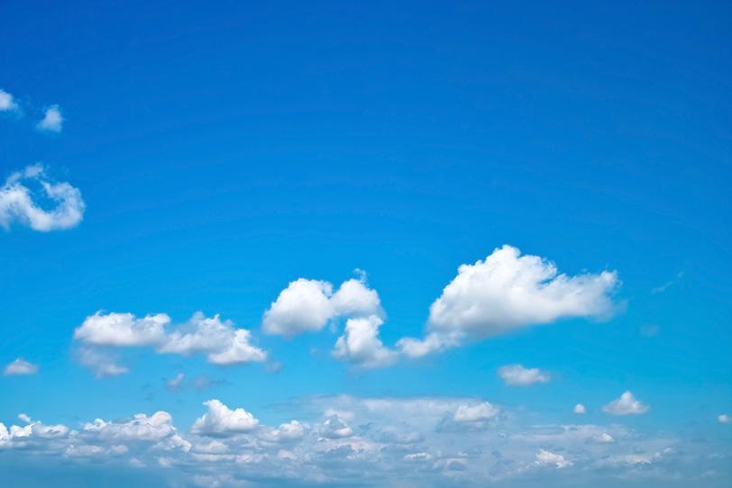 透き通った青空に群がる雲の写真画像