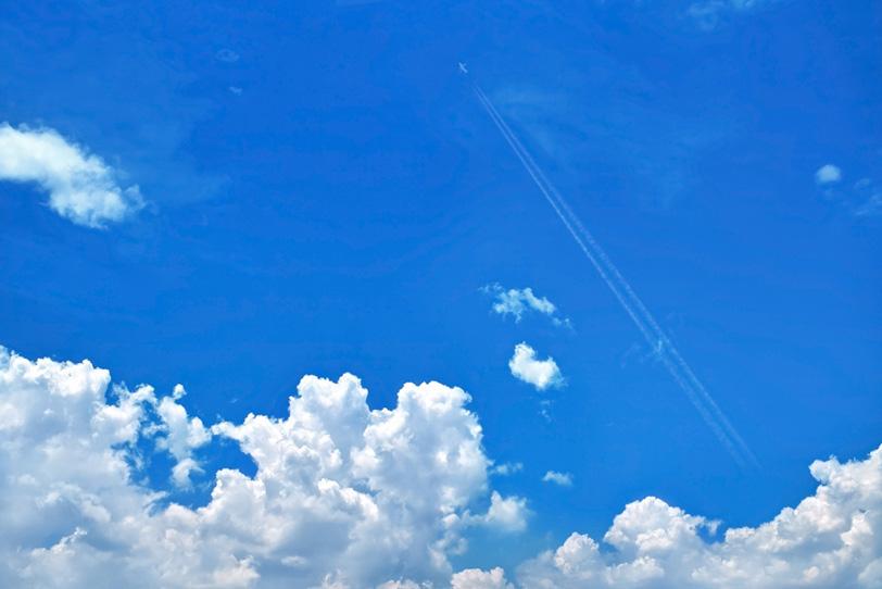 夏の青空を駆け上る飛行機雲の写真画像