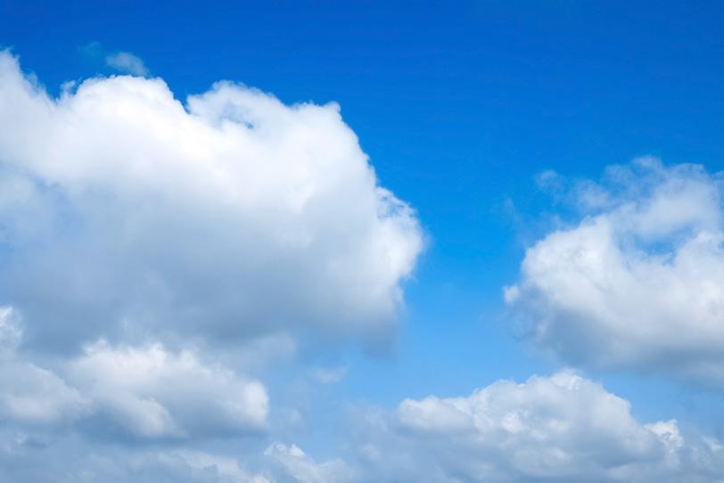 空を這うように流れる積雲群の写真画像