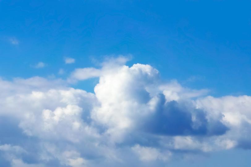 綿のような雲が横に広がる青空の写真画像