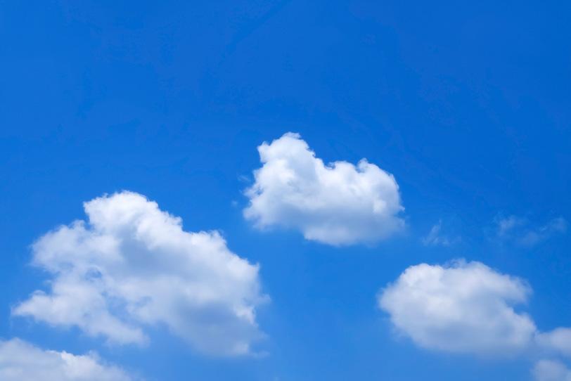 青空にふわふわと流れる白小雲の写真画像