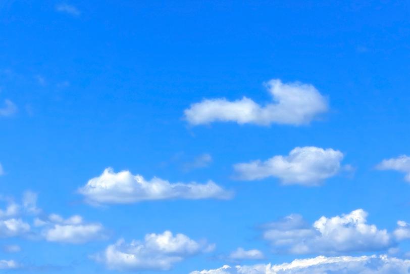 平らな雲が浮かぶ穏やかな青空の写真画像