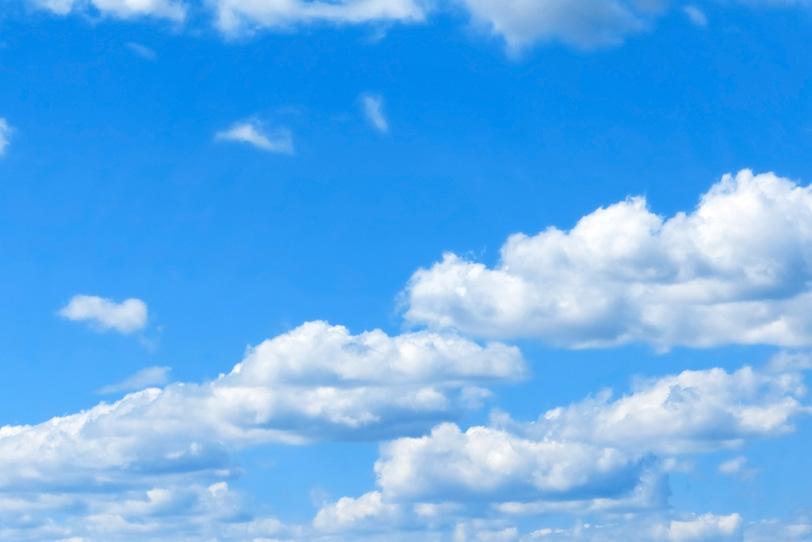 青空に列をなして移動する扁平雲の写真画像