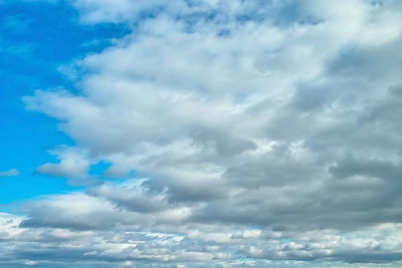 清澄な青空を覆い尽くそうとする雲の写真画像