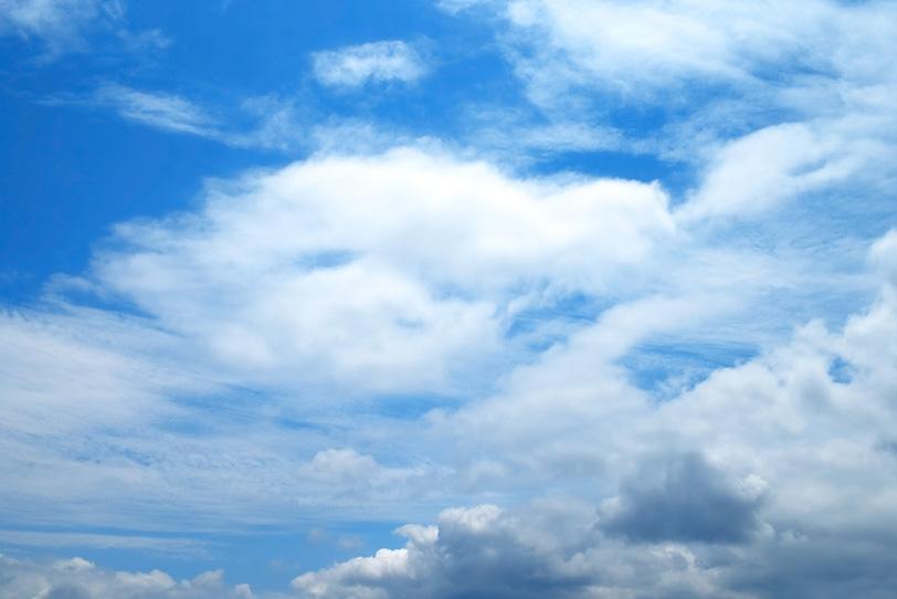 青空に尾を引いて流れる大きな雲の写真画像