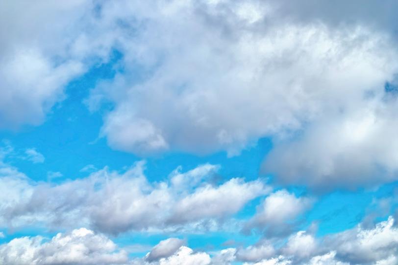 流れる雲の隙間から見える青空の写真画像