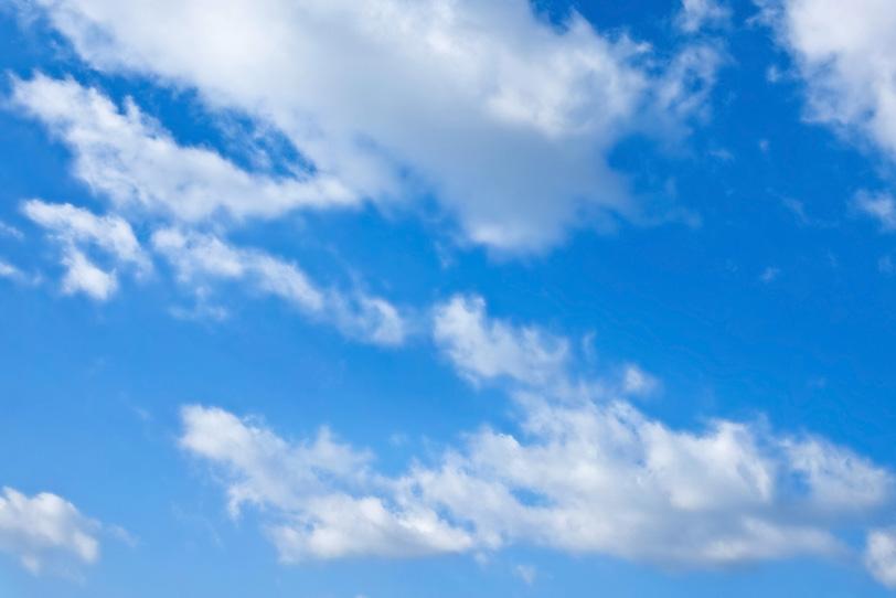 青空を漂う毛羽立った雲の写真画像