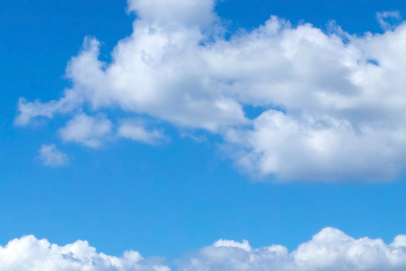 青空を水平に広がる二つの雲の写真画像
