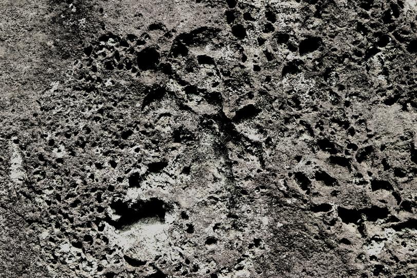 丸い穴が幾つも開いた石の写真画像