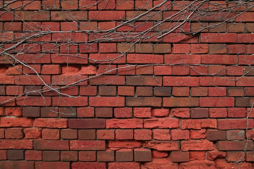 「壊れかけている赤いレンガ壁」