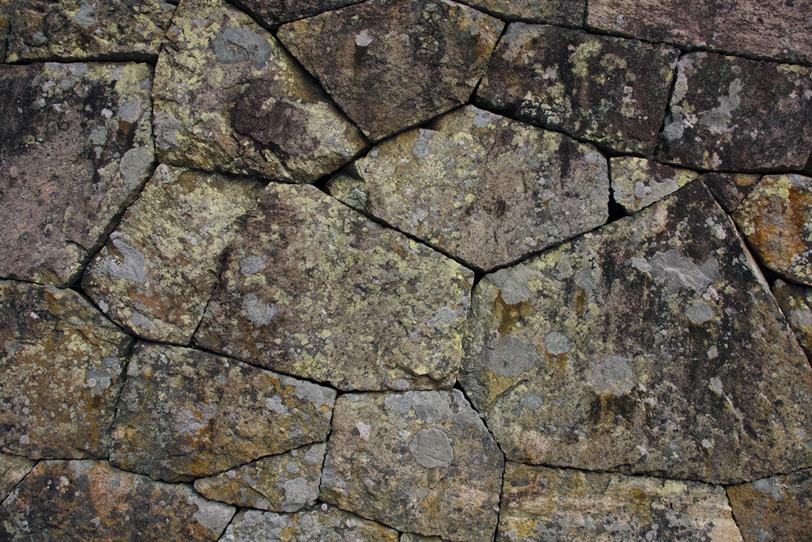 不規則な形の石を隙間なく積んだ壁の写真画像