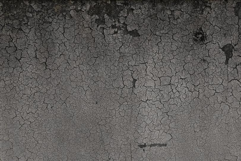 無数にひび割れたモルタルのテクスチャの写真画像