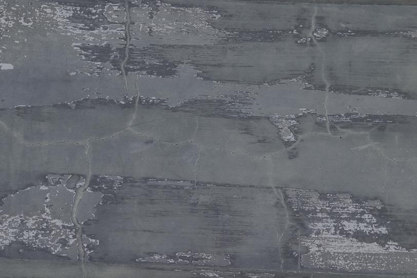 ひび割れと剥がれがあるグレーの壁の写真画像