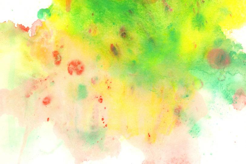 赤緑黄の薄塗りの絵具がにじむ紙の写真画像