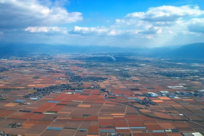 赤い畑が続く広大な平野部にある集落