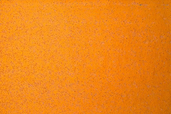オレンジ色に塗装された鉄板に細かい錆が浮き出る(金属 テクスチャのフリー画像)
