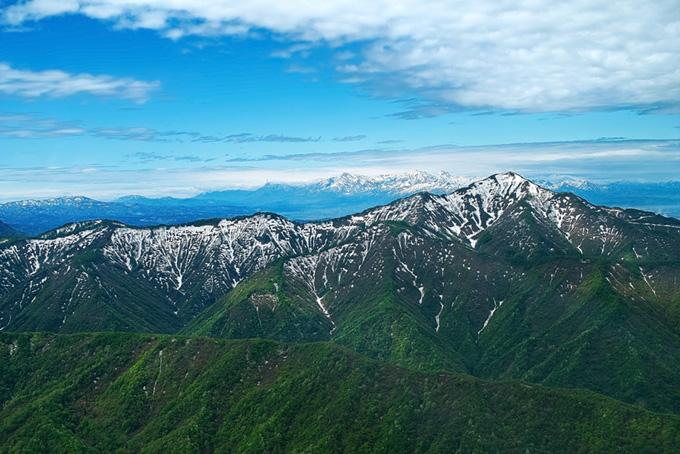 頂きにまだ雪を残す春の山の素材