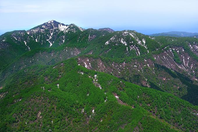 山巓に残る雪と霞空の写真(山 フリーの画像)