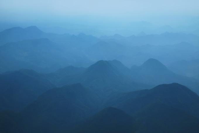 霧で霞んだ水墨画の様な山の風景画像