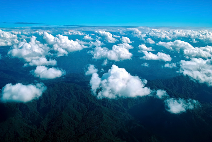 上空から見た果てしなく続く雲とそびえ立つ山々