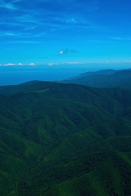 遠くに海が見える緑濃い山岳