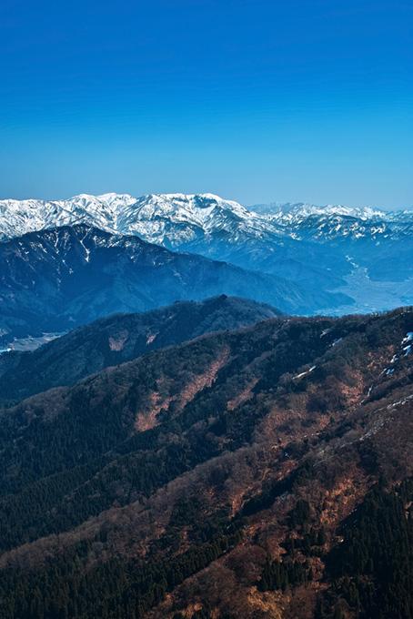 雪解けした山と雪残る山脈