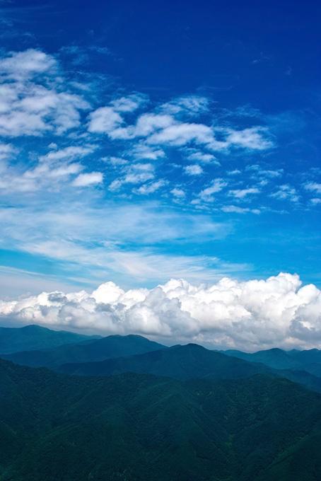 夏空の下に広がる新緑の山々
