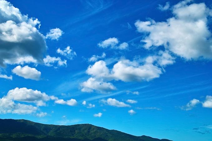 山の上を流れる白い雲の画像