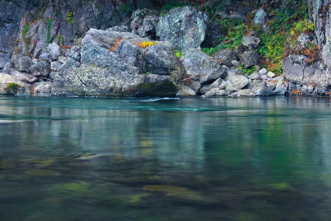 川底が見えるエメラルドグリーンの水と岩