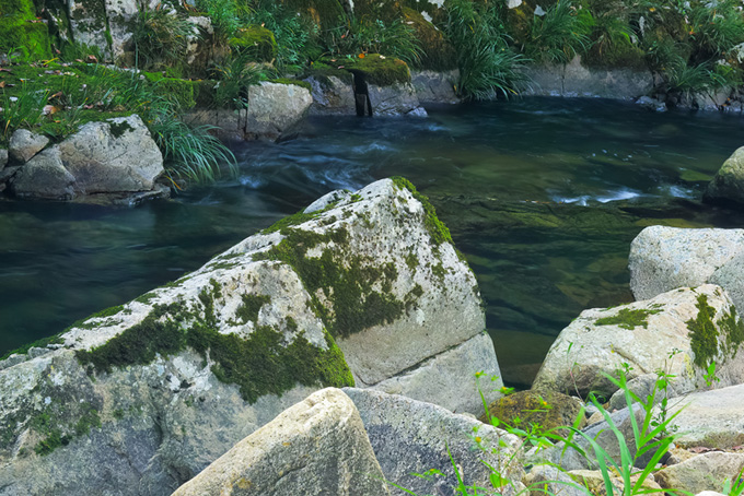 大きな白い岩がある水辺の背景