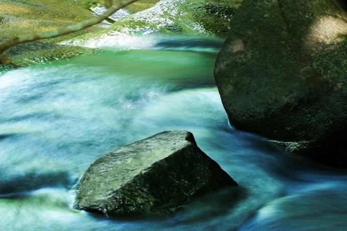 光が差し込む美しい川の流れの背景