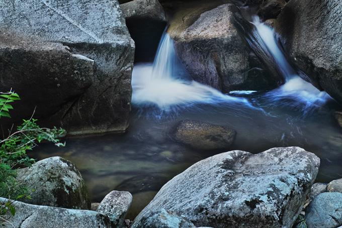 渓流の岩の間を流れる水の写真