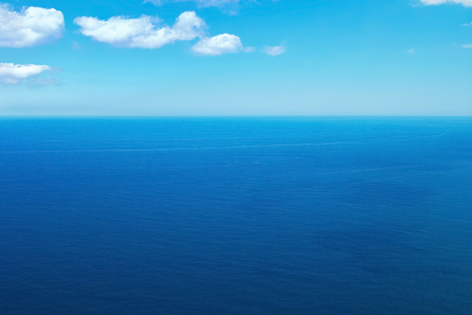 青く広い海の上を流れる雲