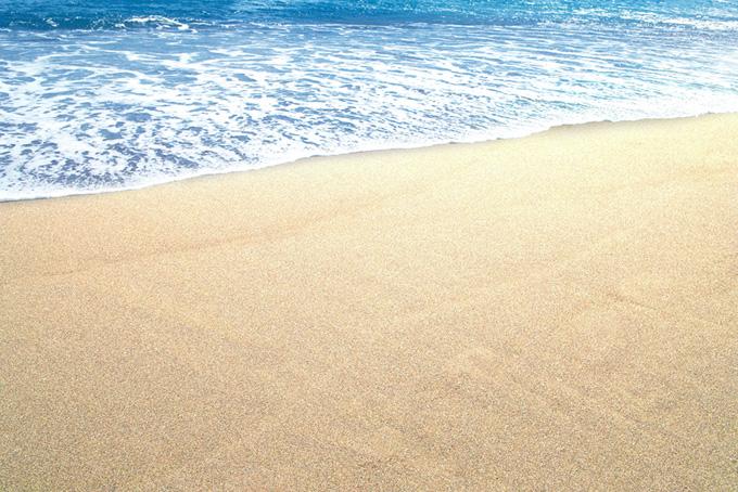 夏の砂浜に寄せる波