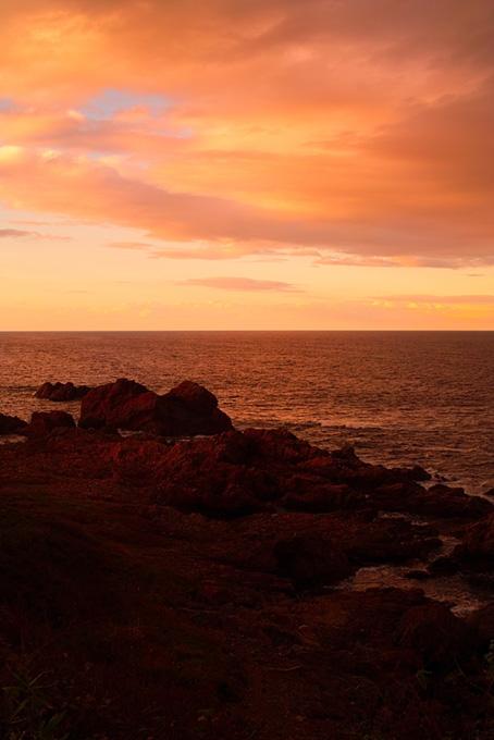 夕焼けの岩の多い海岸