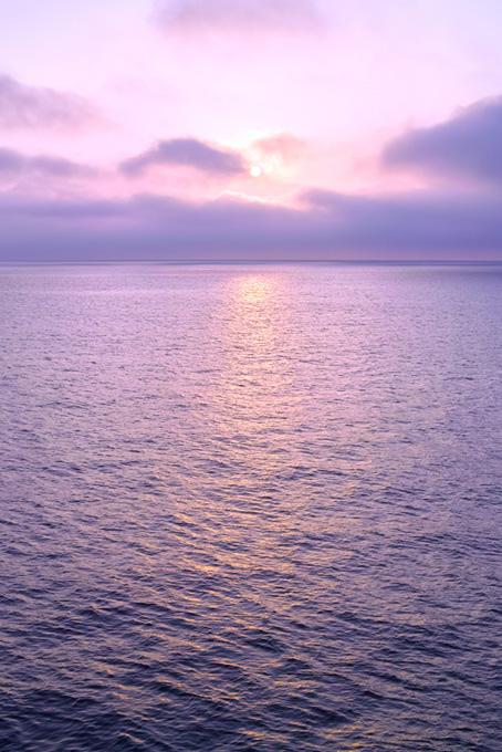 朝日が登る紫色の海