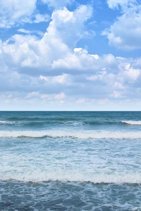 積乱雲と波寄せる夏のビーチ