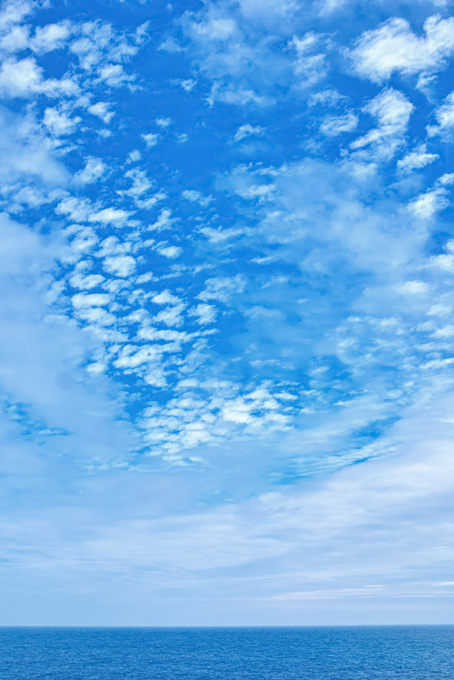 雲が散らばる青空と青い海