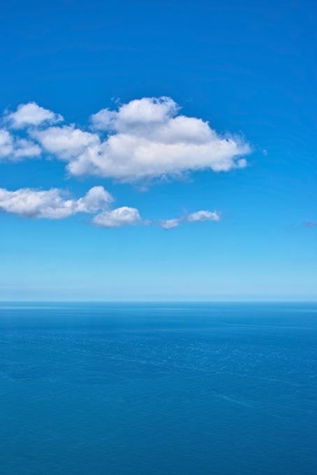水平線に浮かぶ白い雲の画像