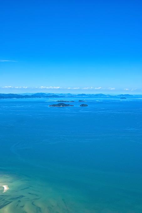 青い海に浮かぶ小さな島々の画像