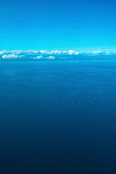 広大な海の向こうの陸地の画像